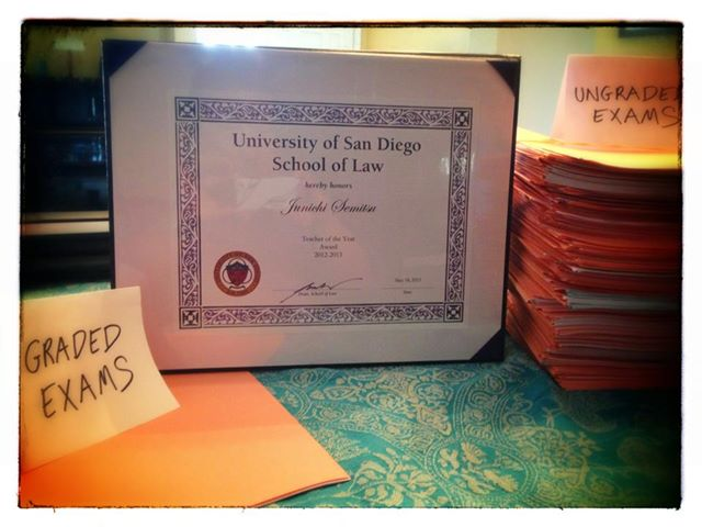 Teacher of the Year Certificate next to a mountain of ungraded exams